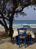 Original greece. Blue table and chairs in the shade of a tree at the cretan coast Stock Photo