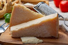 Original italian cheese, aged Parmesan cow milk cheese, pieces and grated Parmigiano-Reggiano. Close up royalty free stock photo