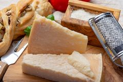 Original italian cheese, aged Parmesan cow milk cheese, pieces and grated Parmigiano-Reggiano. Close up stock photo