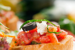 Original Italian fresh bruschetta. Typical finger food, with fresh salad and vegetables on background Royalty Free Stock Photography