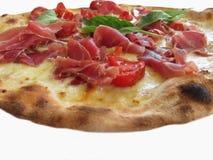 Original italian pizza with ham, tomatoes and fresh basil isolated on white background Royalty Free Stock Image