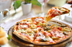 Original Italian seafood pizza. Sliced on wood dish Royalty Free Stock Photos