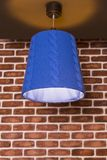 An original knitted lamp hanging on a wall against. A brick wall background Royalty Free Stock Image