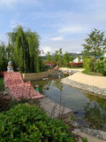 Original landscaping in the theme park, ornamental pond, green trees and bushes, Sochi Park, Russia Stock Photos