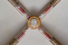 Medieval carved stone Christ head on the ceiling of the entrance hall of a 13th century church stock photography