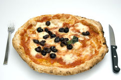 ORIGINAL NEAPOLITAN PIZZA. A juicy handcrafted original neapolitan pizza with fork and knife stock images