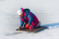 Original Northern fishing. Lapp-woman catches fish under ice watching her through hole. Paatsjoki river, in Arctic circle Royalty Free Stock Photography
