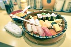 Original plate of sushi nigiri at japanese restaurant in Tokyo. Original plate of nigiri at japanese restaurant in Tokyo city - Vintage filtered look with soft Royalty Free Stock Image