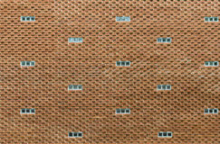 Original red  brick wall with small windows as background Stock Photos