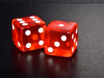 Original Red Casino Gambling Dice on Black Textured Reflecting Background stock photography