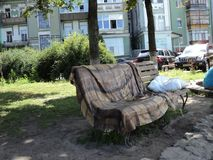 Original sculpture in the city park in the form of a bench and a pillow and blankets lying on it. Interesting original sculpture in the city park in the form of royalty free stock photo