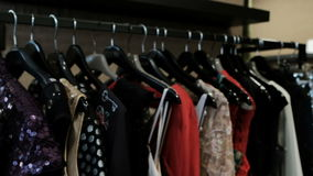 Original things for women hang on a hanger in a fashionable boutique. stock video