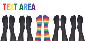 Original Unique Rainbow Socks. A row of socks are lined up on a white isolated background but the middle feet are rainbow colored and original. Use it for a stock image