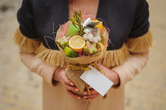 The original unusual edible vegetable and fruit bouquet  with card in woman hands Stock Photo