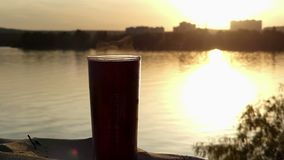 A cup of hot coffee on a lake bank at sunset in summer. An original view of a plastic cup of hot coffee on a picturesque lake bank at a splendid sunset in summer stock video