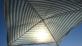 A striped sunshade on the Black Sea coast in summer