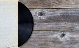 Original vinyl music record in paper holder on aged wood Stock Image