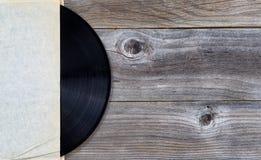 Original- vinylmusikrekord i pappers- hållare på åldrigt trä Fotografering för Bildbyråer