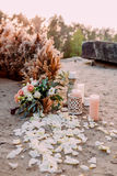 Original wedding floral decoration in the form of mini- bouquets of flowers and candles for ceremony Stock Photo