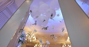 Original wedding floral decoration in the form of mini-vases and bouquets of flowers hanging from the ceiling stock footage