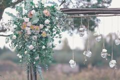 Original wedding floral decoration in the form of mini-vases. And bouquets of flowers hanging from the ceiling Royalty Free Stock Photo