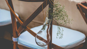 Original wedding floral decoration, mini-vases and bouquets of flowers hanging from the chair Royalty Free Stock Images