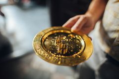 Original wedding rings lie on the steel plate on a table in chur. Man holds golden plate with wedding rings in church Royalty Free Stock Image