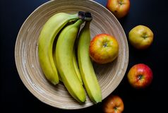 Plate banana. Original wooden plate with continuous lines, apples and bananas on the black table. Organic, natural material of bowl with eternal lines. Eco royalty free stock image