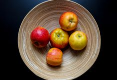 Plate fruit. Original wooden plate with continuous lines and five apples on the black table. Organic, natural material of bowl with eternal lines. Eco-friendly stock photo
