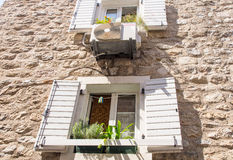 The original wooden shutters on stone wall in old Budva, Montenegro Royalty Free Stock Photo