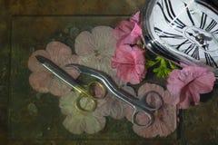 Originalet buktade sax på blommakronbladen av blommor, höger klocka med den krökta vita visartavlan, ovanlig stilleben för inre d Royaltyfri Fotografi