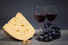 Originalkomposition von gastronomischen Produkten Käse mit einer Weintraube und zwei Gläser Rotwein Stockbilder