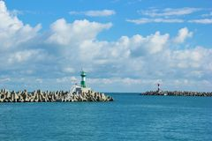 Breakwaters in the blue sea. Originally designed breakwaters with colorful beacons. calm sea and blue sky with some clouds stock photo