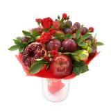 Origineel fruitig boeket die uit appelen, pruimen, peren, granaatappel en bloemen van scharlaken rozen in een glasvaas bestaan op stock foto's