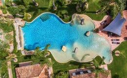 Originele decoratieve pool in de tuin met palmen, luchtmening stock afbeelding
