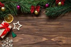 Originele Kerstmis hengelde expositie met een giftdoos, sneeuwvlok, ster, spar, plak van citroen op de houten achtergrond royalty-vrije stock fotografie