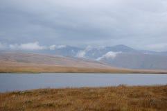 Orilla de la estepa de un lago con la hierba amarilla seca en el fondo de las altas montañas de la roca Imagen de archivo