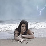 Orilla de la playa del clima tempestuoso con la mujer joven foto de archivo libre de regalías