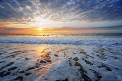 Orilla de la playa en la puesta del sol con algunas personas que practica surf Fotos de archivo libres de regalías