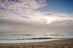 Orilla de la playa Vista de la arena y del cielo con el sol y las nubes Imagen de archivo libre de regalías