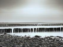 Orilla de mar Báltico en fuerte viento Rompeolas construido de registros de madera imagenes de archivo