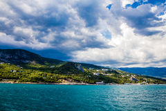 Orilla de mar contra la perspectiva de las montañas y del cielo con las nubes Imagen de archivo