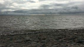 Orilla de Mar del Norte en Frisia del este Ostfriesland, Alemania con el cielo dramático Mar tranquilo y ondas bajas almacen de metraje de vídeo