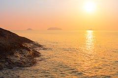 Orilla de mar rocosa contra el sol poniente Naturaleza Foto de archivo