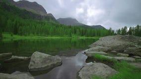 Orilla de un lago cubierto por la hierba y las rocas delante de las montañas altas almacen de metraje de vídeo