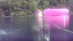 Orilla del agua y vista subacuática del bikini que lleva de la mujer bastante joven y de las gafas de sol púrpuras que nadan en p almacen de metraje de vídeo