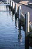 Orilla del embarcadero en el puerto deportivo con los bolardos de madera y el mar azul, vert imagen de archivo libre de regalías
