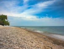 Orilla del lago con las arenas rocosas y el cielo azul fotos de archivo libres de regalías