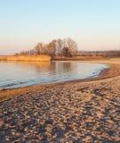 Orilla del lago de Sandy y agua ondulada imagenes de archivo