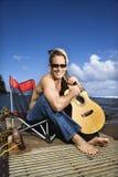 Orilla del lago del hombre joven y guitarra el sostenerse que se sientan Imagen de archivo libre de regalías
